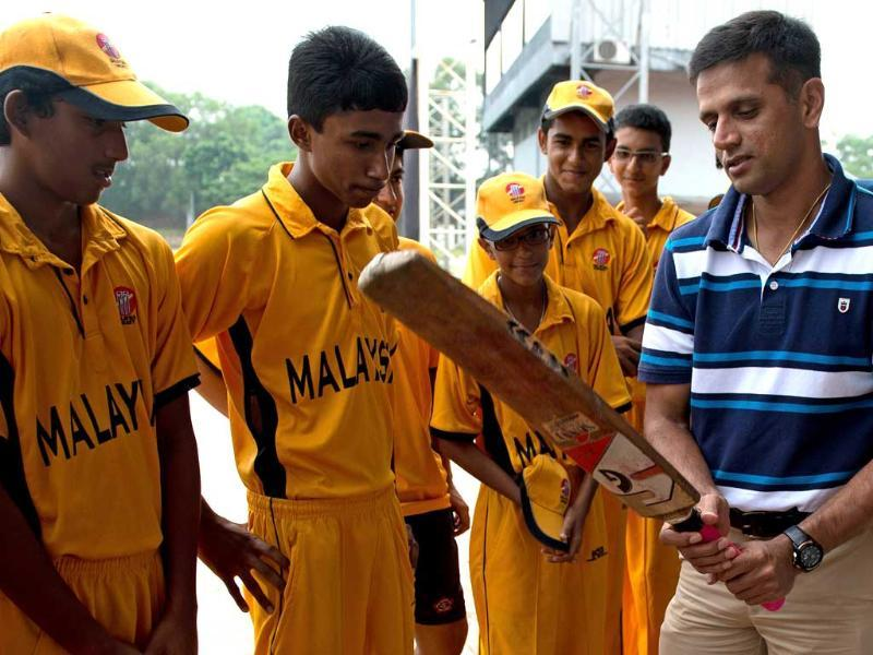 Former Indian cricket team skipper Rahul Dravid (R) teaches batting techniques to Malaysian U-16 cricketers during a training clinic in Kuala Lumpur. AFP/Saeed Khan