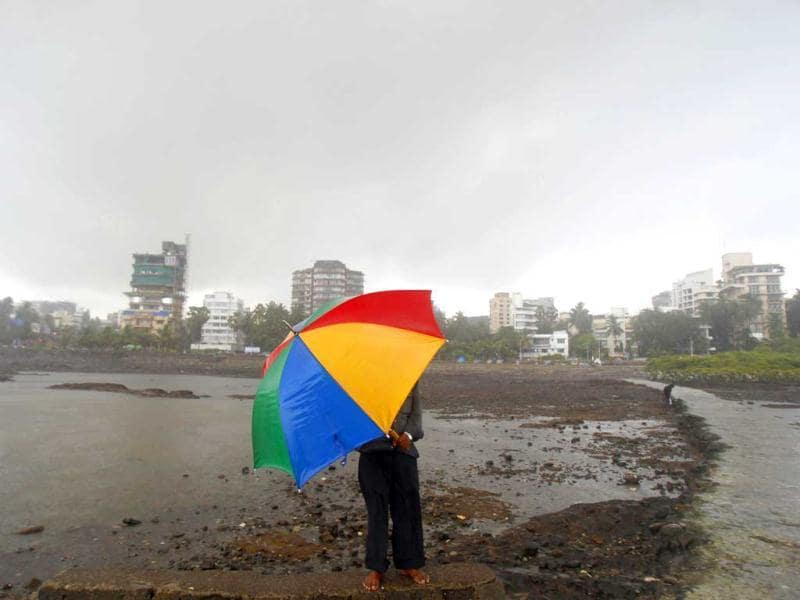 A man holds an umbrella against the wind on the shore of the Arabian sea during a monsoon shower in Mumbai. AP Photo/Rafiq Maqbool