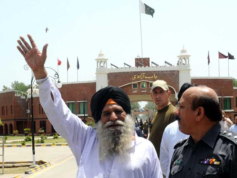 Freed Indian prisoner Surjeet Singh, escorted by Pakistani security officials, waves before leaving Pakistan for India at the Wagah border. AFP/Arif Ali