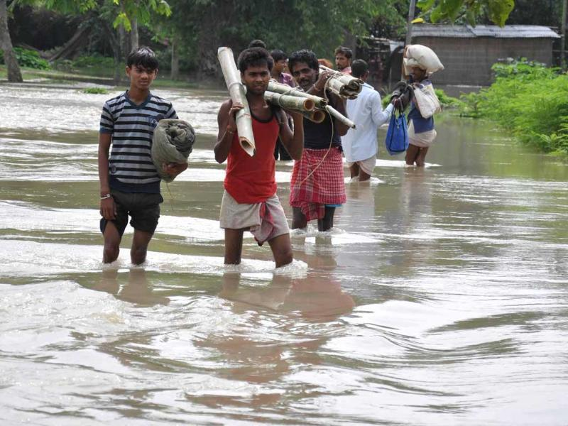 Villagers cross a water logged street in flood affected village Bhuragaon, Marigaon district in Assam.