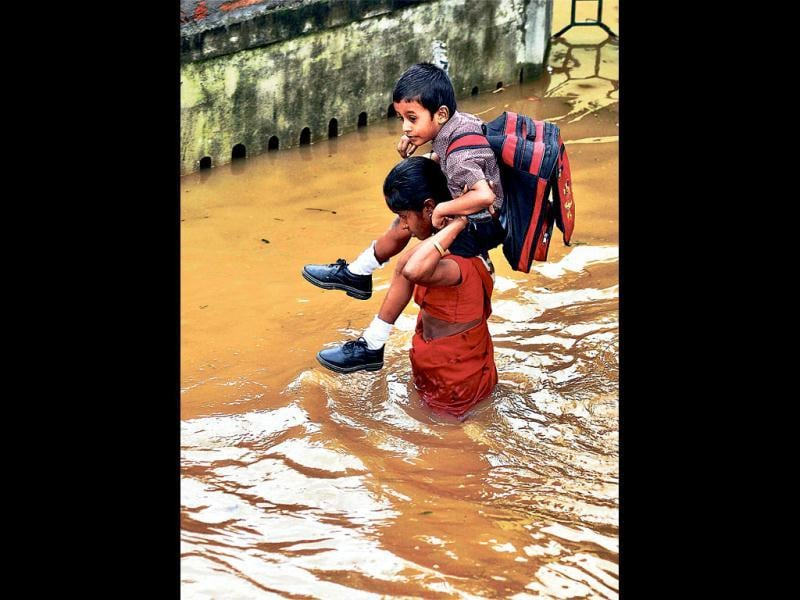 A woman carries a child to school through a flooded street of Anil Nagar in Guwahati. (PTI Photo)