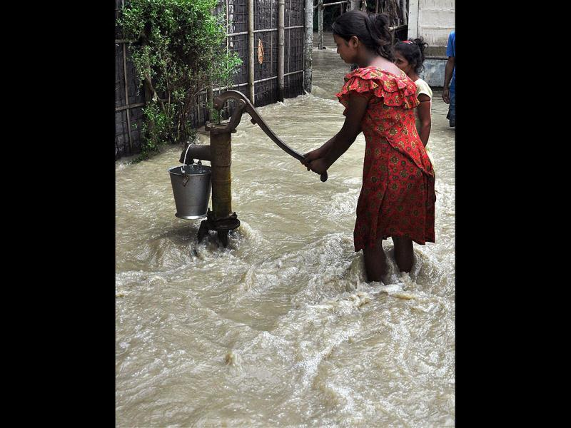 A girl pumps water from a hand pump, as flood water flows into Pachim Khuradai under Nalbari District in Assam. (PTI Photo)