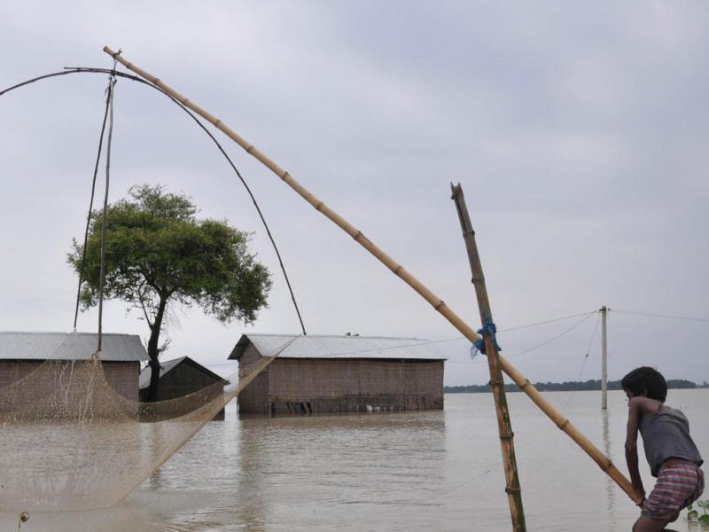 A boy fishes in flood affected Asigarh village in Marigaon district of Assam. (UNI Photo)