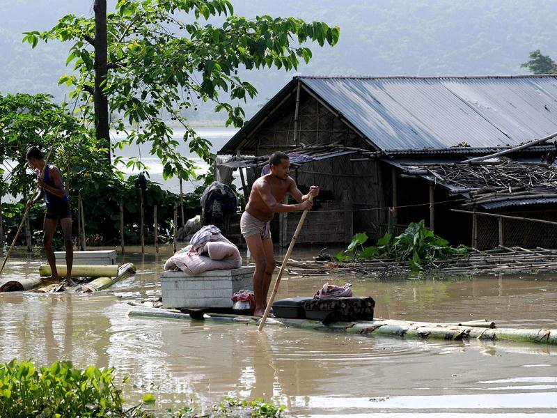 A villager moves his belongings on a banana raft from his half submerged house in flood waters at the flood affected area at Mayong village in Morigoan district, some 80 kms from Guwahati. (AFP Photo)