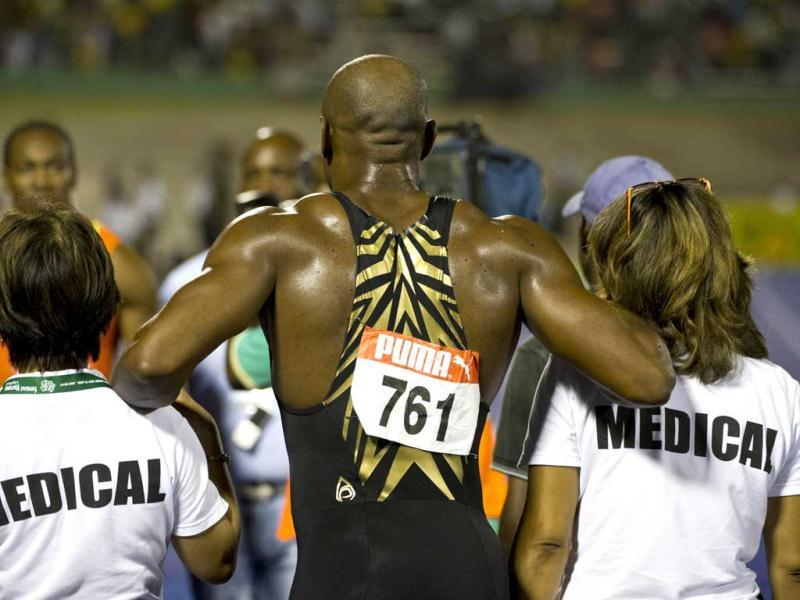 Jamaican sprinter Asafa Powell leaves the track escorted by medical personel after finishing third in the 100m men's final of the Jamaican Olympic Athletic Trials at the National Stadium in Kingston. AFP/Mladen Antonov