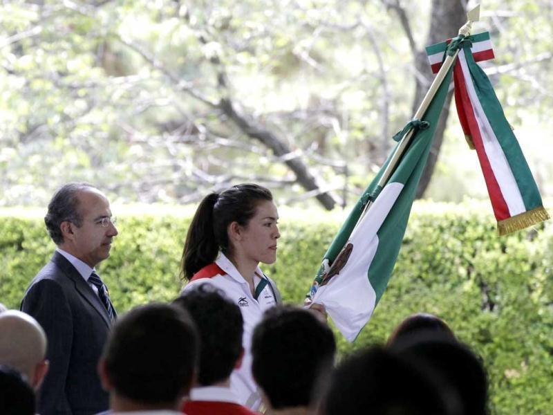 Maria del Rosario Espinoza, 67kg taekwondo Olympic gold medallist (R), holds up the Mexican flag after it was officially delivered by Mexican President Felipe Calderon (L) at the official presidential residence Los Pinos in Mexico City. Reuters/Henry Romero