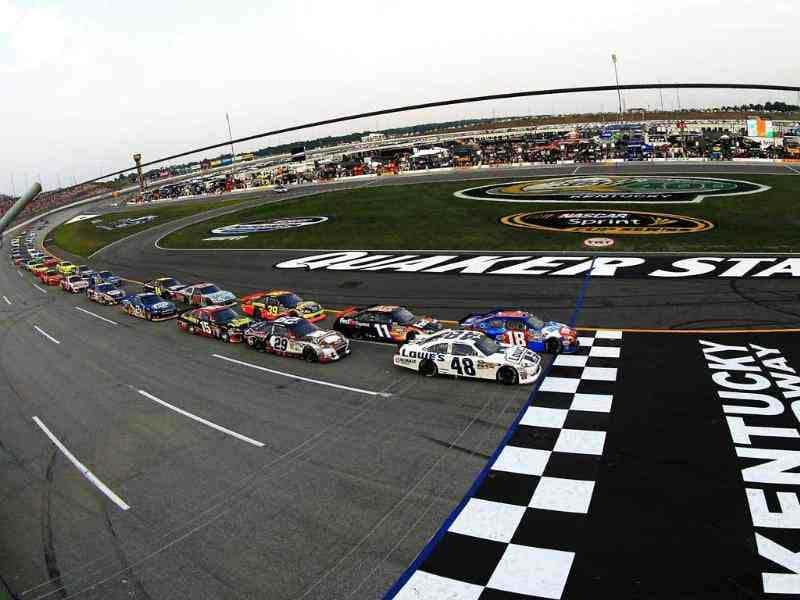 Jimmie Johnson, driver of the #48 Lowe's Dover White Chevrolet, and Kyle Busch, driver of the #18 Red-White-Blue Toyota, lead the field to the green flag to start the NASCAR Sprint Cup Series Quaker State 400 at Kentucky Speedway in Sparta, Kentucky. AFP/Chris Trotman