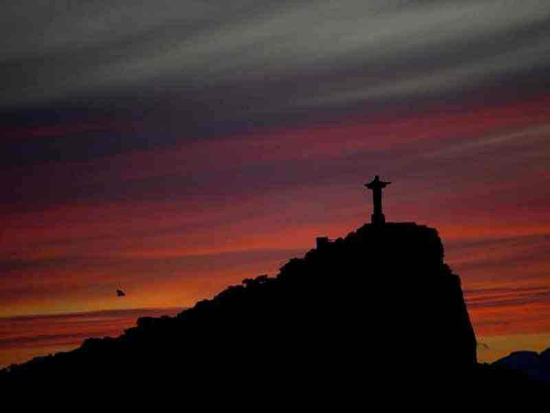 View of the statue of Christ the Redeemer (L), atop Corcovado Hill, at sunrise in Rio de Janeiro, Brazil. AFP Photo / Christophe Simon