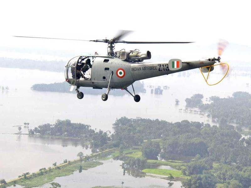 An Indian Air Force (IAF) helicopter, carrying relief supplies, flies over the flooded areas of the Sonitpur district, Assam. Reuters/Stringer