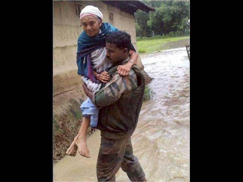 An Army jawan rescues an old woman from a flood affected village in Assam. Incessant heavy rains have caused massive flooding and landslides in the state. PTI Photo
