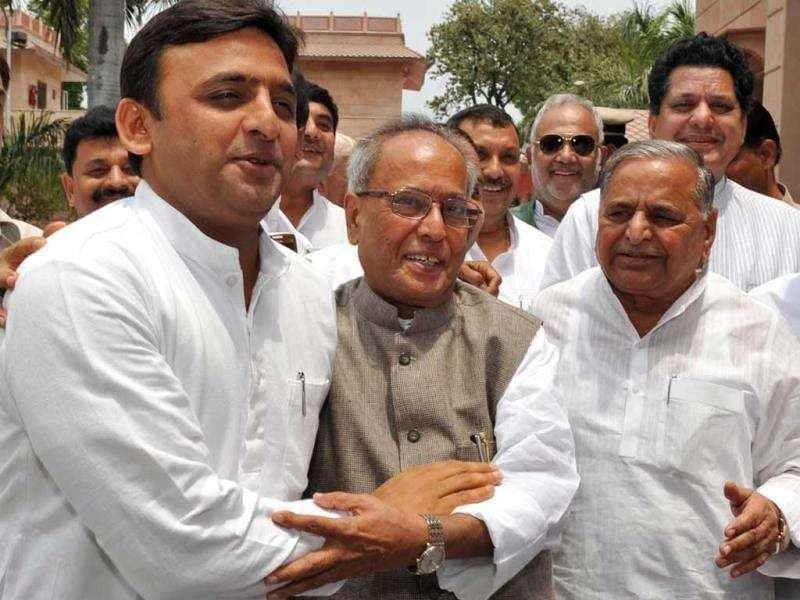 Uttar Pradesh chief minister Akhilesh Yadav (L) embraces Pranab Mukherjee (C) while Samajwadi Party chief Mulayam Singh Yadav looks on during a meeting in Lucknow. AFP/STR
