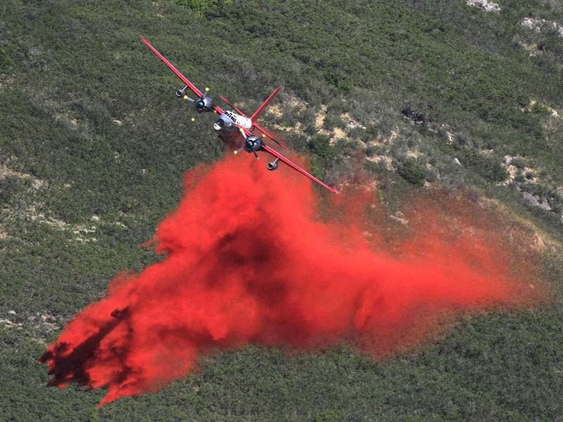 A plane drops slurry on the Quail Fire in Alpine, Utah, July 3, 2012. The fire started this afternoon and spread quickly through the eastern end of Alpine and then up the mountain side. It is still out of control. REUTERS/George Frey