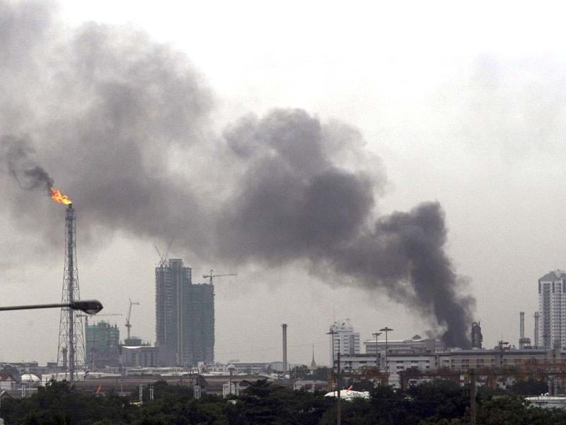 Black smoke billows after an explosion at the Bangchak oil refinery and depot in Bangkok, Thailand. AP Photo/Sakchai iLalit