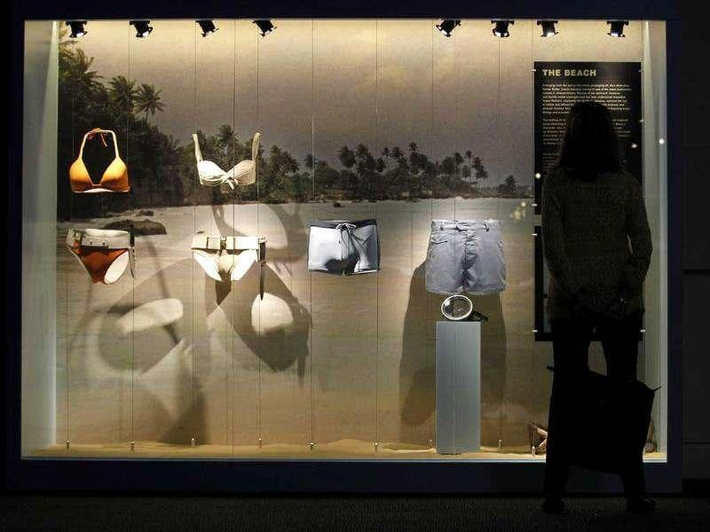 A visitor looks at a display showing, from left, an orange bikini worn by Jinx, by actress Halle Berry, in the film 'Die Another Day', a white bikini worn by Honey Ryder by actress Ursula Andress in film Dr No, James Bond's, actor Daniel Craig swimming trunk in film 'Casino Royale' and James Bond's, actor Sean Connery beach shorts in the film 'Thunderball' in the exhibition 'Designing 007 - Fifty Years of Bond Style' at the Barbican centre in London. (AP Photo/Sang Tan)