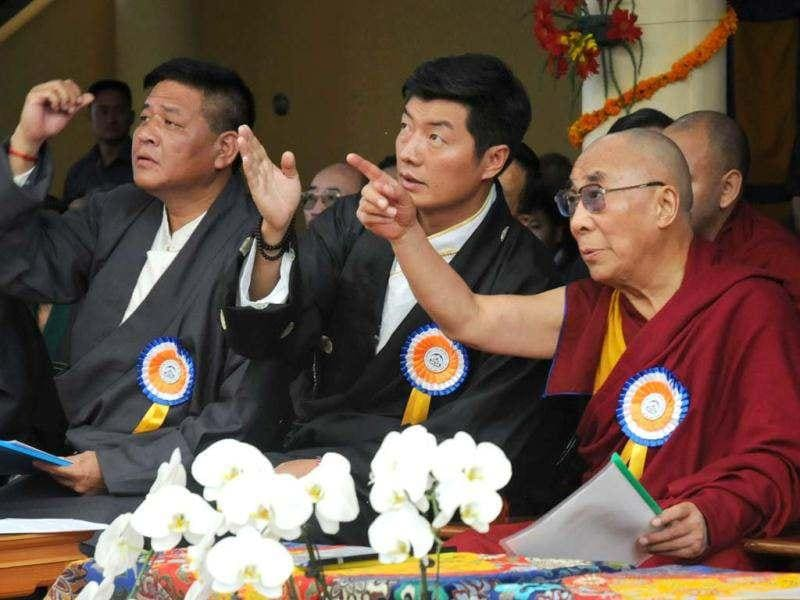 Tibetan spiritual leader The Dalai Lama (R), exile Tibetan Prime Minister Lobsang Sangay (C), and Speaker of the Tibetan Parliament-in-exile Penpa Tsering (L) gesture to a banner showing pictures of the Dalai Lama at different ages during his 77th birthday celebrations at the Tsuglakhang Temple in McLeod Ganj, Dharamsala. (AFP Photo)