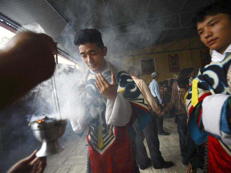 Tibetans dressed in traditional attire takes blessings from the rising smoke of incense while participating in the 77th birthday celebrations of exiled spiritual leader the Dalai Lama in Kathmandu. Nepal ceased issuing refugee papers to Tibetans in 1989 and recognizes Tibet to be a part of China. (Reuters)