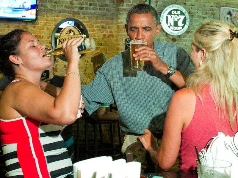 US President Barack Obama (C) shares a beer with Suzanne Woods (R) and Jennifer Klanac (L) during at Ziggy's Pub and Restaurant Amherst, Ohio, July 5, 2012, during an unannounced visit while on a bus tour of Ohio and Pennslyvania. AFP Photo/Jim Watson