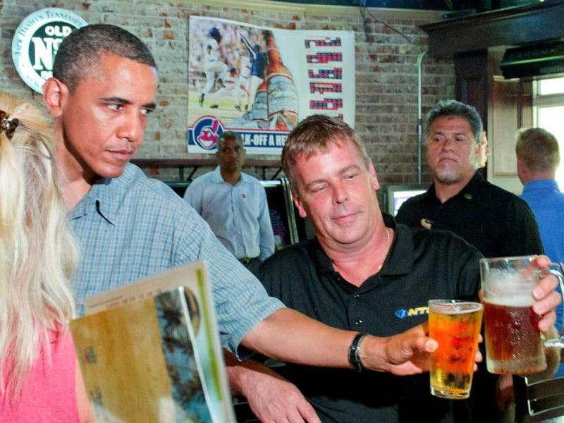 US President Barack Obama (C) toast with a bar patron at Ziggy's Pub and Restaurant Amherst, Ohio, July 5, 2012, during an unannounced visit while on a bus tour of Ohio and Pennslyvania. AFP Photo/Jim Watson