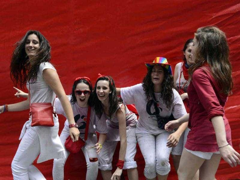 Revellers pose in front of a red tarpaulin during the start of the San Fermin Festival in Pamplona. The festival, best known for its daily running of the bulls, kicked off with the traditional