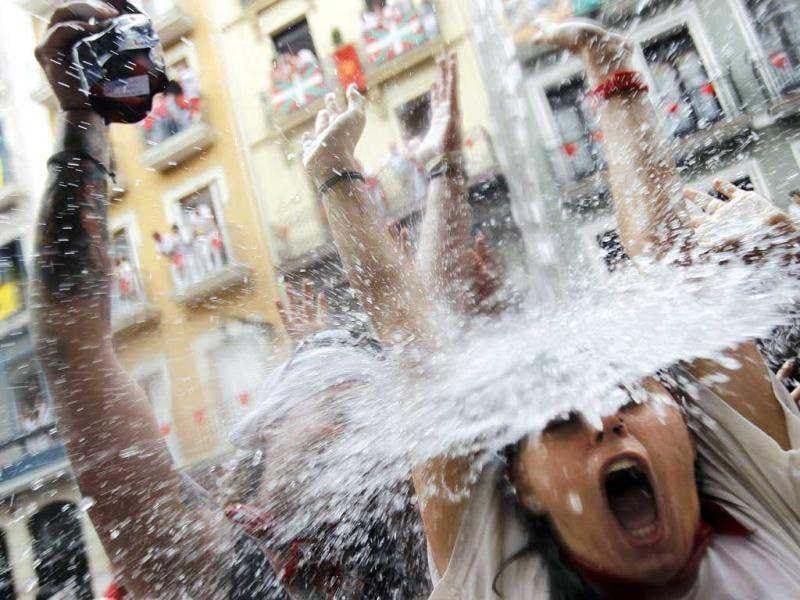 A reveller gets soaked in water thrown from a balcony during the start of the San Fermin Festival in Pamplona. The annual festival, best known for its daily running of the bulls, kicked off with the traditional