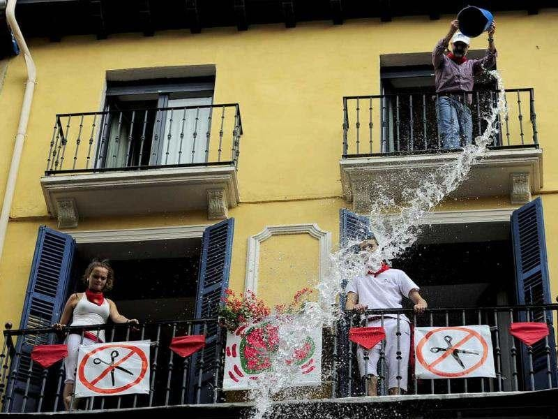 Reveler enjoys pouring water down from a balcony during the 'Chupinazo', the official opening of the San Fermin fiestas in Pamplona, northern Spain to celebrate the start of Spain's most famous bull-running festival. Perhaps best glorified by Ernest Hemingway's 1926 novel