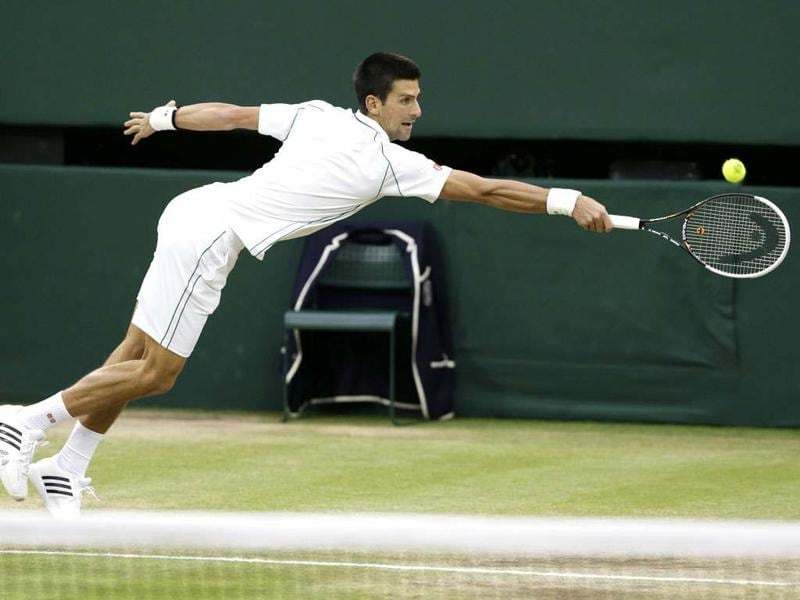 Novak Djokovic of Serbia plays a shot to Roger Federer of Switzerland during a men's semifinals match at the All England Lawn Tennis Championships at Wimbledon, England. AP Photo/Kirsty Wigglesworth