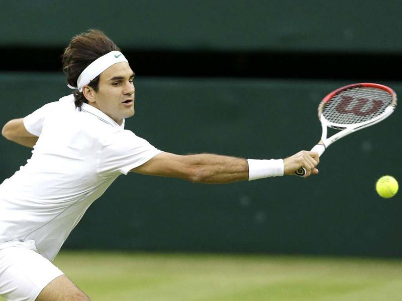 Roger Federer of Switzerland plays a shot to Novak Djokovic of Serbia during a men's semifinals match at the All England Lawn Tennis Championships at Wimbledon, England. AP Photo/Kirsty Wigglesworth