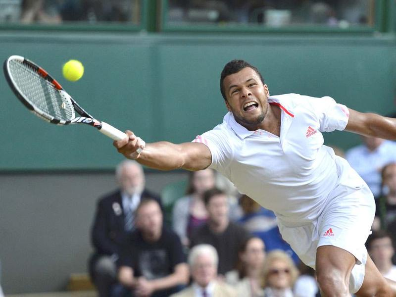 Jo-Wilfried Tsonga of France hits a return to Andy Murray of Britain during their men's semi-final tennis match at the Wimbledon tennis championships in London.  REUTERS/Toby Melville