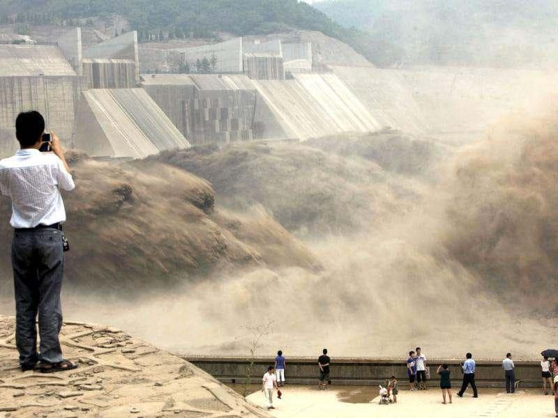 Visitors gather to watch giant gushes of water being released from the Xiaolangdi dam to clear up the sediment-laden Yellow river and to prevent localized flooding, in Jiyuan, central China's Henan province. China is hit by big downpours every summer often causing fatalities as seen in 2010, which saw the nation's worst flooding in a decade leaving more than 4,300 people dead or missing. (AFP Photo)