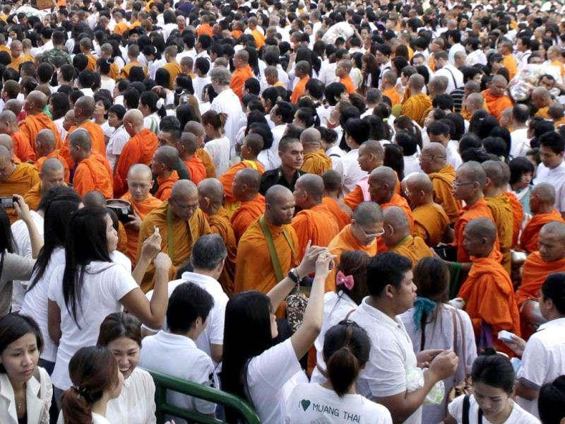 Thais gather to offer non-perishable food to 12,600 Buddhist monks during an alm offering to celebrate the 2,600th anniversary of the enlightenment of the Lord Buddha in downtown Bangkok, Thailand. (AP Photo/Xinyan Yu)