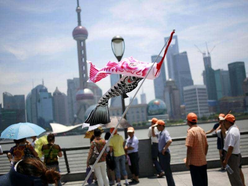 A tour guide hoists carp streamers to signal her customers at the Bund, one of the most famous landmarks in Shanghai in China. (AP Photo/Eugene Hoshiko)