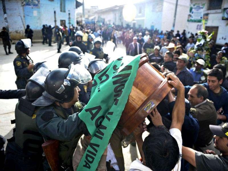 Peruvian police block the way to people carrying the coffins of three of the demonstrators who died during the protests against the Conga mining project in Celendin, Cajamarca, Peru. (AFP Photo/Ernesto Benavides)
