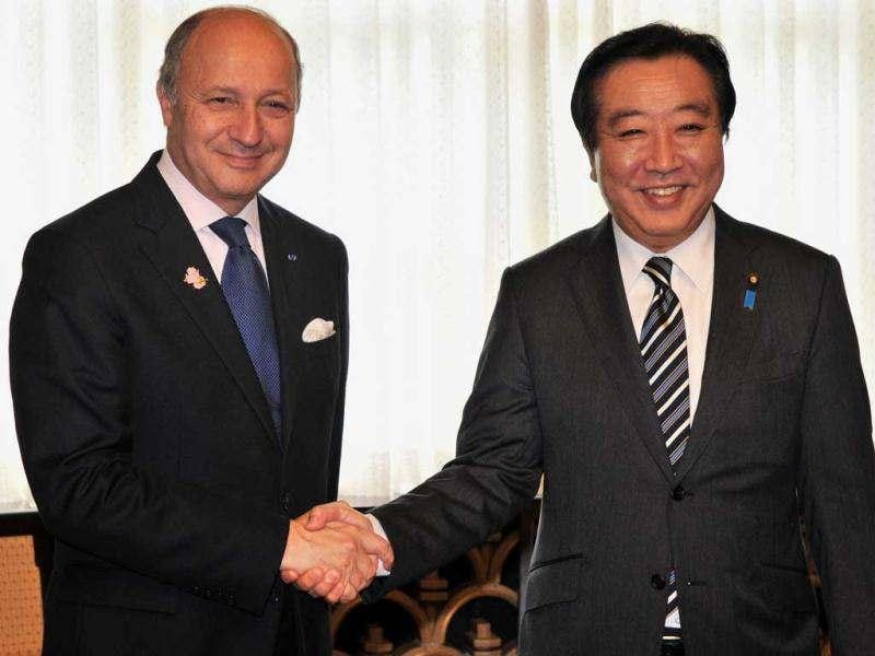 France's foreign minister Laurent Fabius (L) shakes hands with Japanese Prime Minister Yoshihiko Noda prior to their talks at Noda's residence in Tokyo. Fabius is now here to attend the Tokyo Conference on Afghanistan, aimed at charting a course for Afghanistan once foreign combat forces leave in 2014.  AFP Photo / Yoshikazu Tsuno