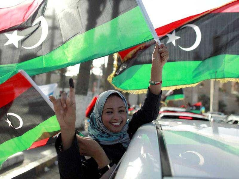 A woman celebrates on the streets after casting her vote during the National Assembly election in Tripoli's Martyrs square. Crowds of joyful Libyans, some with tears in their eyes, parted with the legacy of Muammar Gaddafi on Saturday as they voted in the first free national election in 60 years. Reuters/Zohra Bensemra