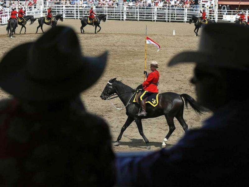 Cowboys watch the Royal Canadian Mounted Police musical ride. Reuters/Todd Korol