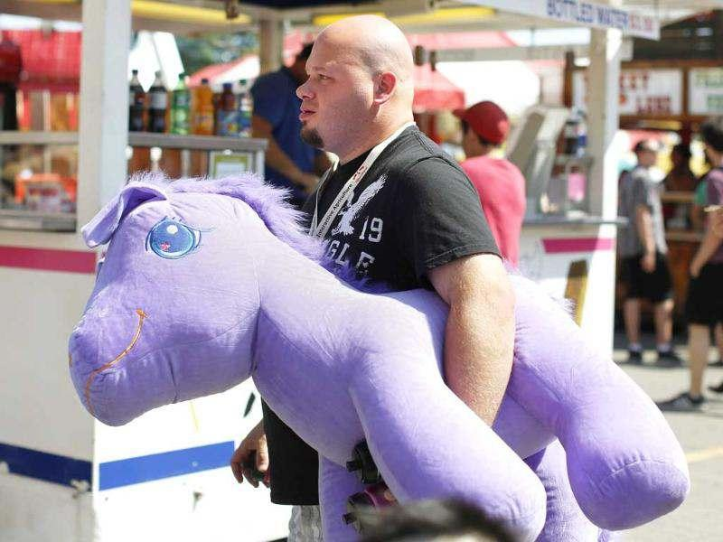 Kelsy Hosack carries his plush purple horse he won on the midway during the 100th anniversary of the Calgary Stampede. Reuters/Todd Korol