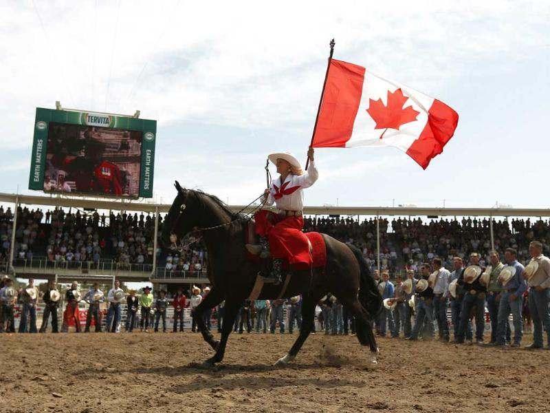A country girl carries the Canadian flag while O' Canada is played before the start of the Stampede Rodeo. Reuters/Todd Korol