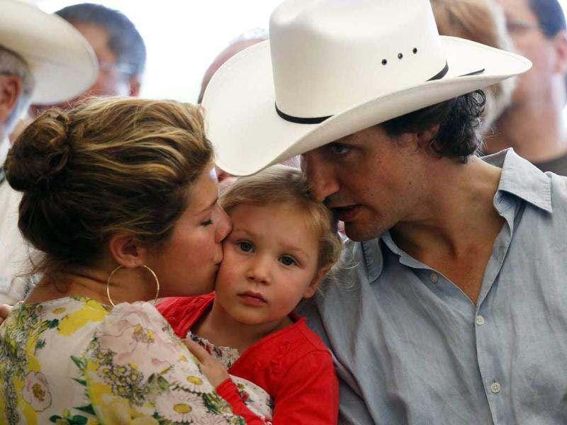Liberal Member of Parliament Justin Trudeau and his wife Sophie kiss their daughter Ella-Grace during the Liberal Stampede breakfast. Reuters/Todd Korol