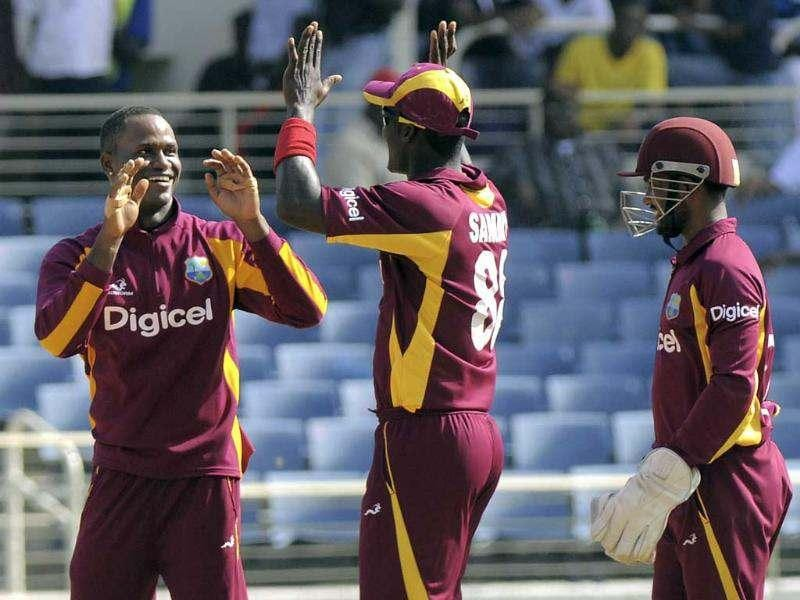 West Indies' Marlon Samuels, left, Captain Darren Sammy, center, and wicket keeper Denesh Ramdin high five while celebrating the fall of the wicket of New Zealand's Tom Latham during their second One-Day International cricket match in Kingston, Jamaica. AP/DigicelCricket.com