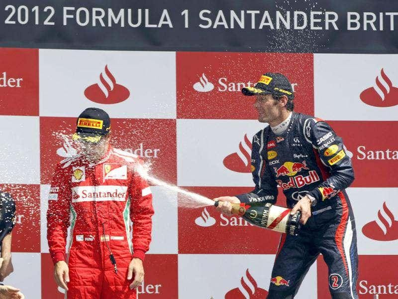 Australia's Red Bull Formula 1 driver Mark Webber, right, who won the Formula One British Grand Prix, sprays champagne to Spain's Ferrari Formula 1 driver Fernando Alonso, who finished second, at the Silverstone circuit, Silverstone. AP/Lefteris Pitarakis
