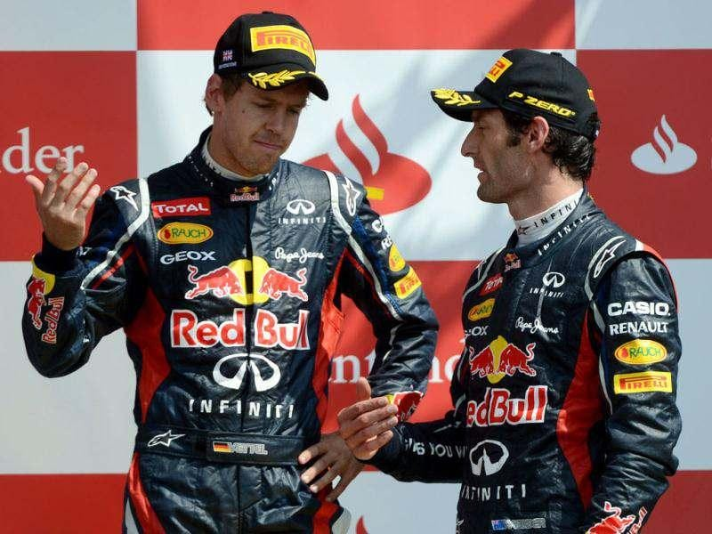 Red Bull Racing's Australian driver Mark Webber (R) and Red Bull Racing's German driver Sebastian Vettel chat on the podium at the Silverstone circuit during the British Formula One Grand Prix. AFP/Dimitar Dilkoff