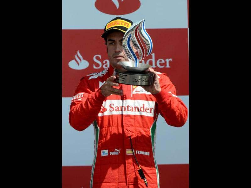 Ferrari's Spanish driver Fernando Alonso celebrates on the podium at the Silverstone circuit during the British Formula One Grand Prix. AFP/Dimitar Dilkoff