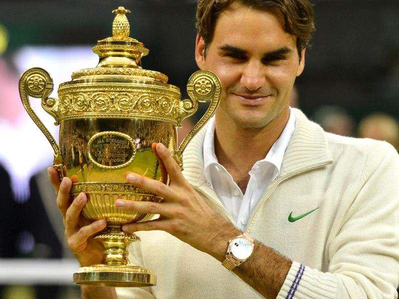 Switzerland's Roger Federer celebrates with the trophy after his men's singles final victory over Britain's Andy Murray during Wimbledon Championships tennis tournament at the All England Tennis Club in Wimbledon, southwest London. AFP/Leon Neal