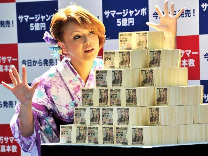 Japanese actress Yuko Nakazawa poses with 500 million yen ($6.25 million) as tickets went on sale for the 500 million yen summer Jumbo Lottery in Tokyo. Thousands of punters queued up for tickets in the hope of becoming a millionaire. AFP/Yoshikazu Tsuno
