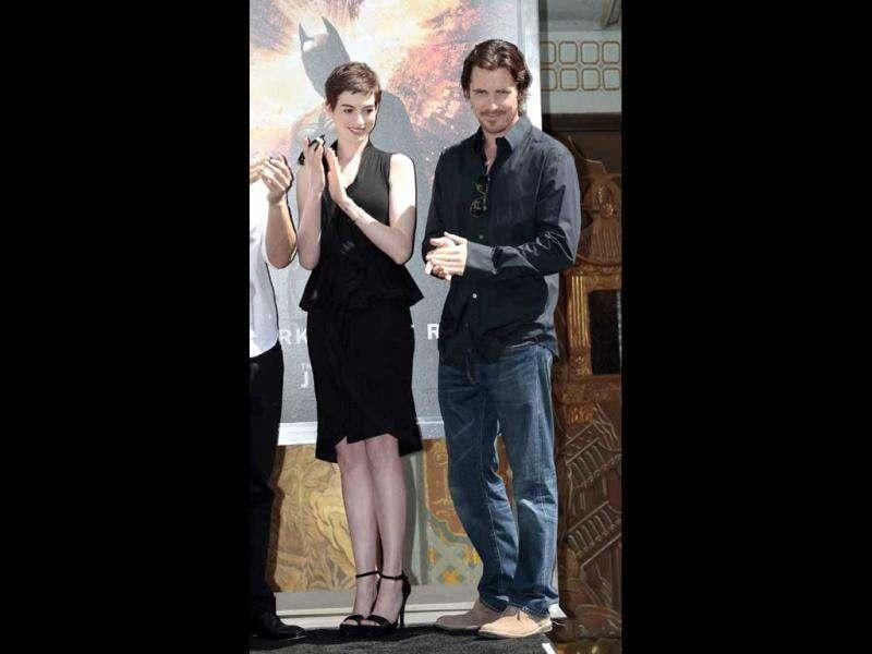 Actors Christian Bale and Anne Hathaway (L) applaud during a hand and footprint ceremony for director Christopher Nolan in the forecourt of the Grauman's Chinese Theatre in Hollywood, California.