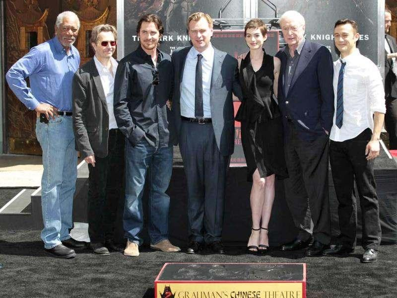 Director Christopher Nolan (C) poses with the prominent Dark Knight Rises actors (from L-R) Morgan Freeman, Gary Oldman, Christian Bale, Anne Hathaway, Michael Caine and Joseph Gordon-Levitt, at his hand and footprint ceremony in the forecourt of the Grauman's Chinese Theatre in Hollywood, California.