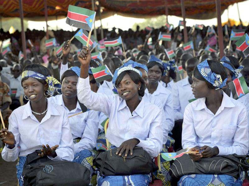 Women wave South Sudanese flags as they attend the country's anniversary celebrations, at the John Garang mausoleum in Juba. AP Photo/Shannon Jensen