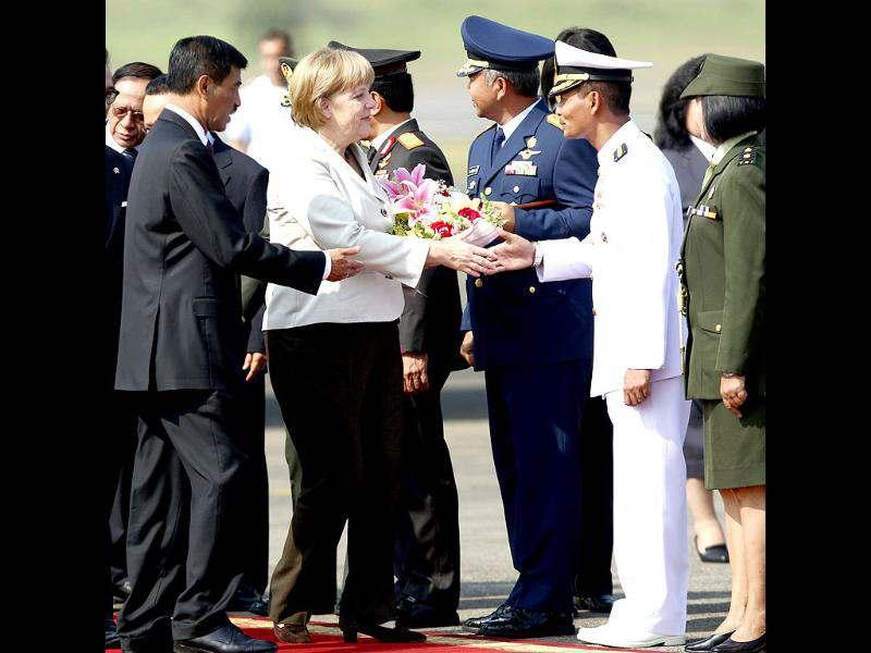 German Chancellor Angela Merkel, center, is greeted by Indonesian military officials upon arriving at Halim Perdanakusuma airport in Jakarta, Indonesia. AP/Tatan Syuflana
