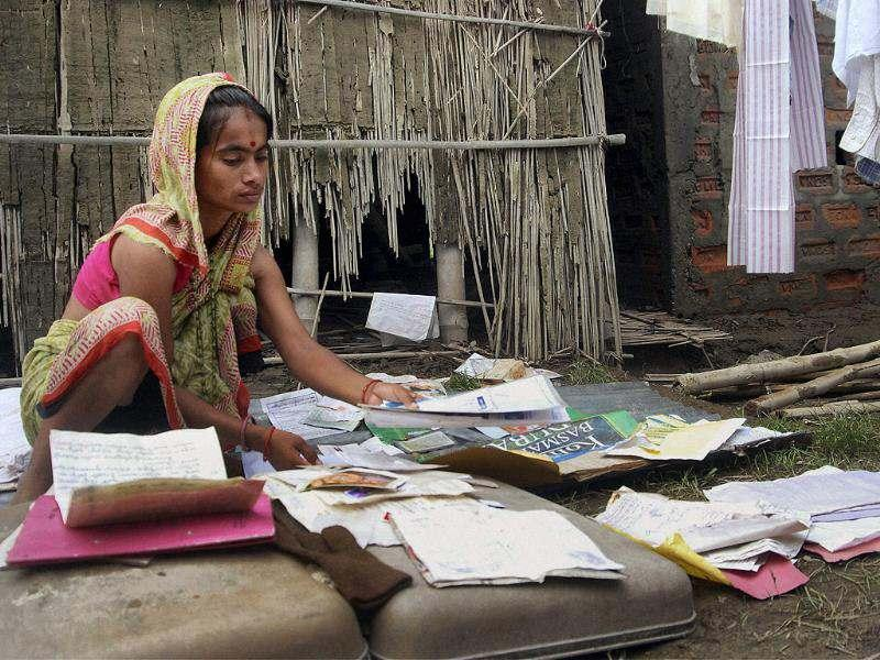 A flood-affected woman sifting through documents damaged in floods at Vatki village in Sonitpur, Assam. PTI photo