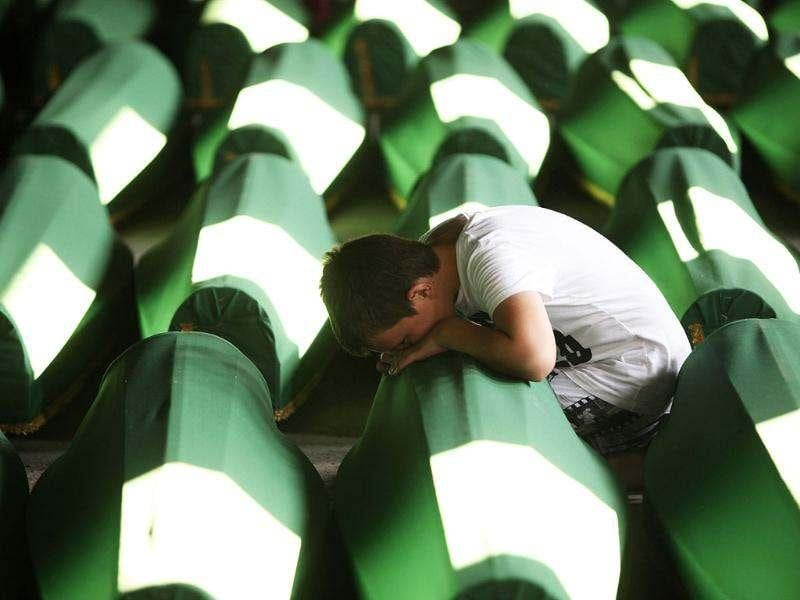 A Bosnian Muslim boy cries near coffins prepared for a mass burial at the Memorial Center in Potocari, near Srebrenica. Reuters/Dado Ruvic
